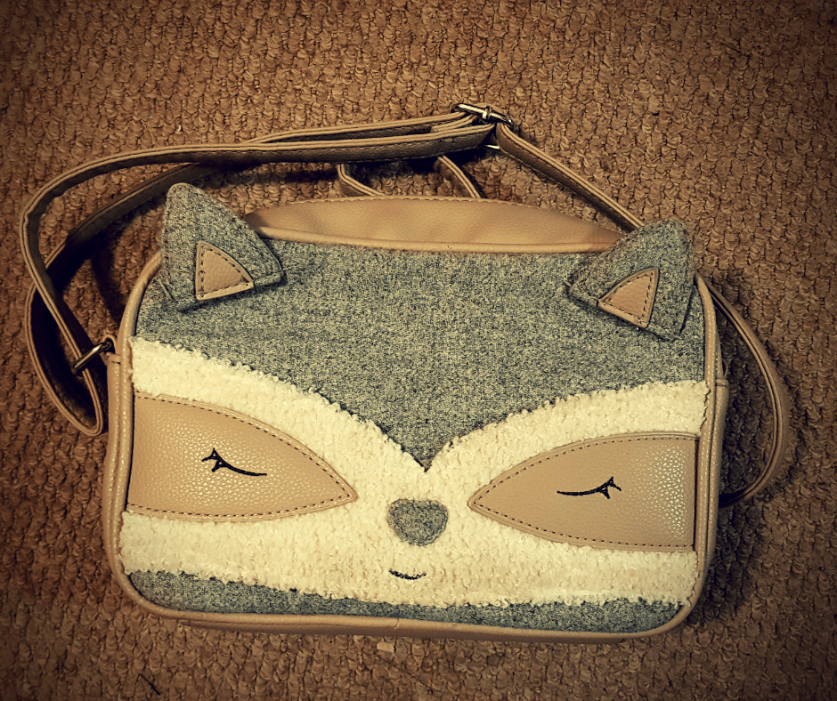 Grey and Beige over the shoulder hand bag designed to look like a raccoon face.