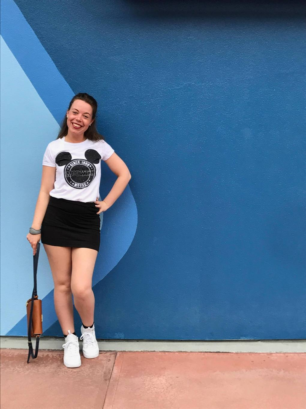 A girl with Mickey mouse t-shirt and black skirt in front of a blue wave patterned wall