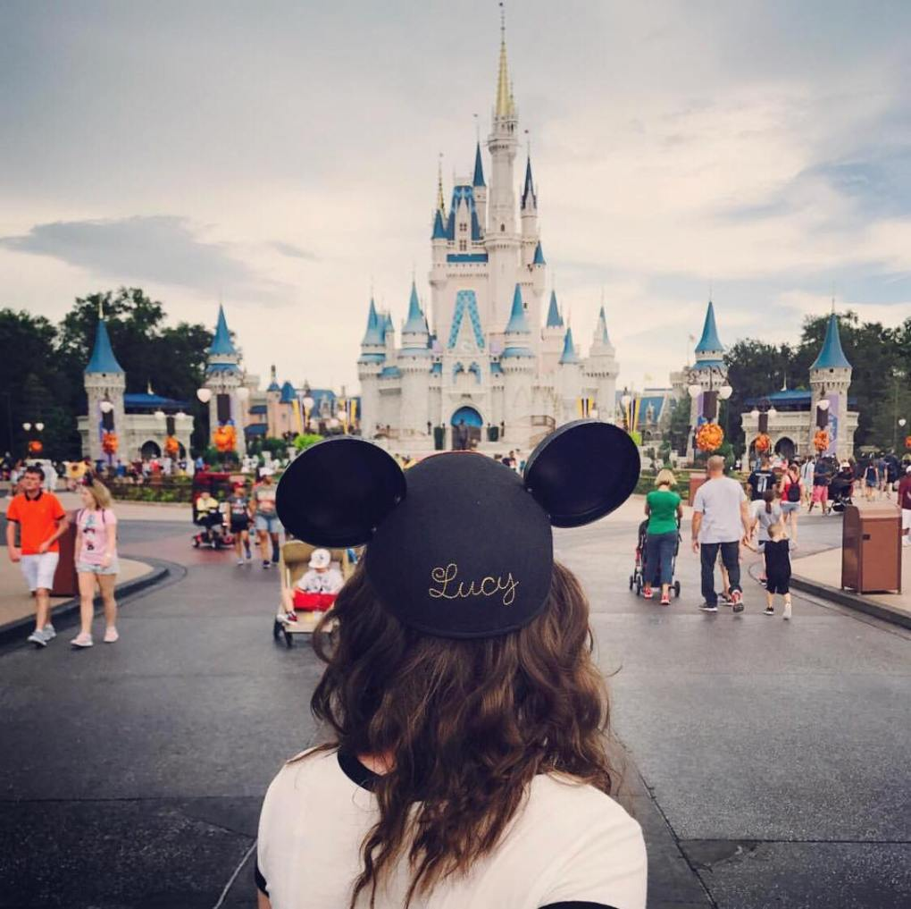 A girl with Mickey hat with Lucy written on it standing in front of the grey Cinderella Castle at Disney World