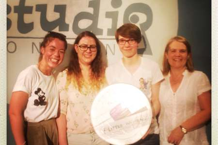 Four women stand in front of a sign saying secret studio London and holding a silver film reel with little women written on it.