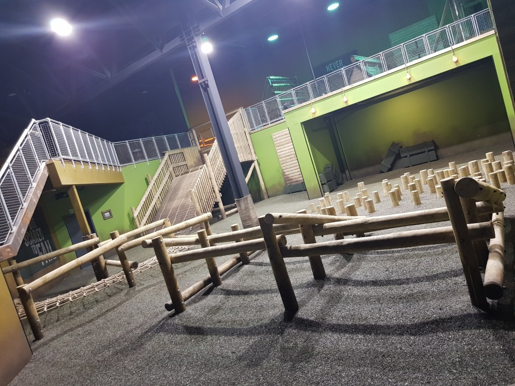 The Assault course at the Bear Grylls Adventure, Birmingham. Wooden stepping stones, poles for going under and over, a net to crawl under and a steep slope to climb up.