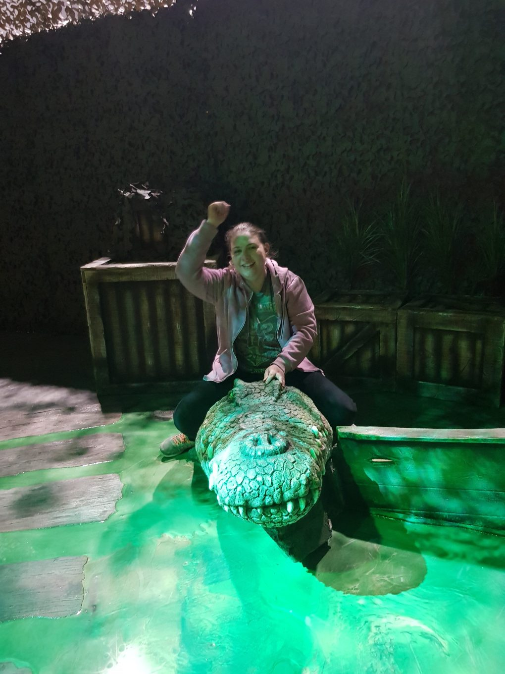 A girl wearing a grey shirt and purple hoodie riding a crocodile figure.