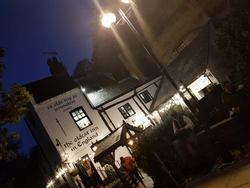 Outside of Ye Olde Trip to Jerusalem. A White pub with black roof. Outside sits Gary the Co-owner of the Original Nottingham Ghost Walk