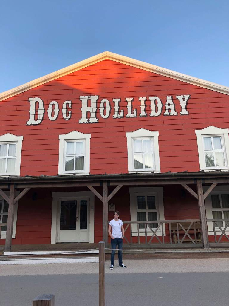 A girl standing in front of a building in the Hotel Cheyenne. A wild west style red barn type building saying Doc Holiday in white writing