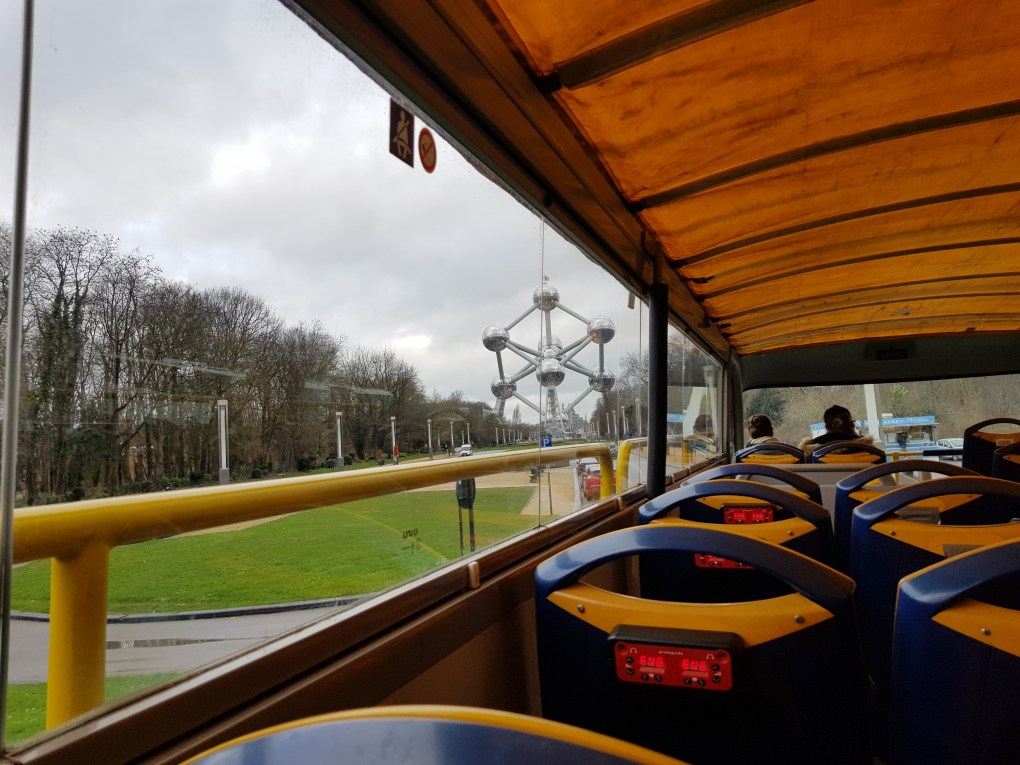 Inside of a double decker sightseeing bus with a view of the Atomium from the side. The Atomium is a large metal sculpture in the shape of an atom