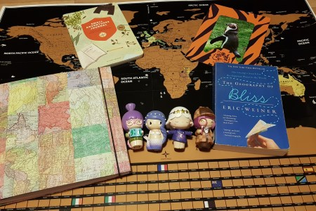 A few travel items that make great gifts for travelers. A black and gold scratch off world map, a scrapbook with a map of the world, a book called the Small Adventure Journal, a book called The Geography of Bliss, a picture of a penguin in a Dudley Zoo tiger striped frame and four momiji dolls, a traveler holding a map, a mermaid, a girl wearing a star dress and headband and a detective doll.