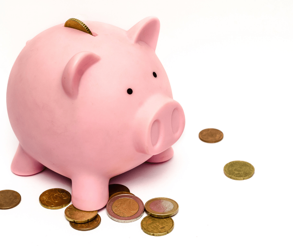 a pink piggy bank with coins scattered around it