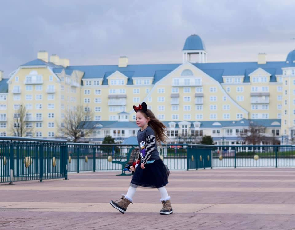 A little girl wearing Minnie Mouse ears outside the Newport Bay Club hotel. A pale yellow building with a blue roof