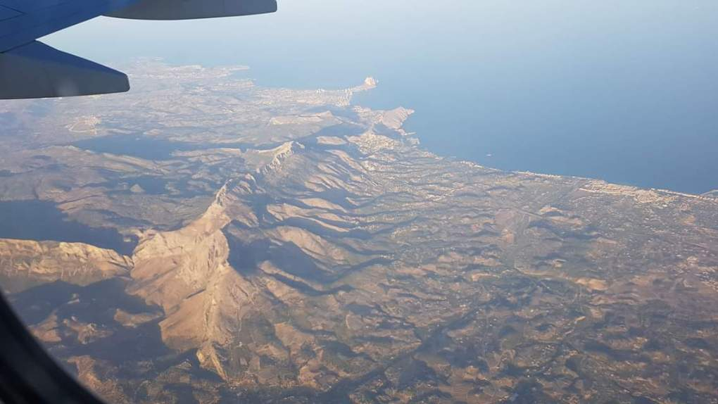 A view outside of an aeroplane window with a view of the ocean and a mountain range