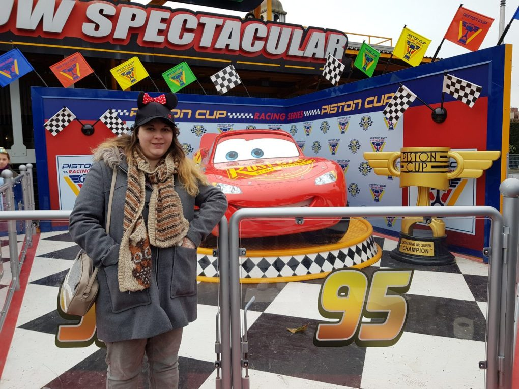 A girl stood in front of a car designed to look like lightning Mcqueen with red paint and eyes instead of a window. Next to him stands a large trophy with Piston Cup written on it