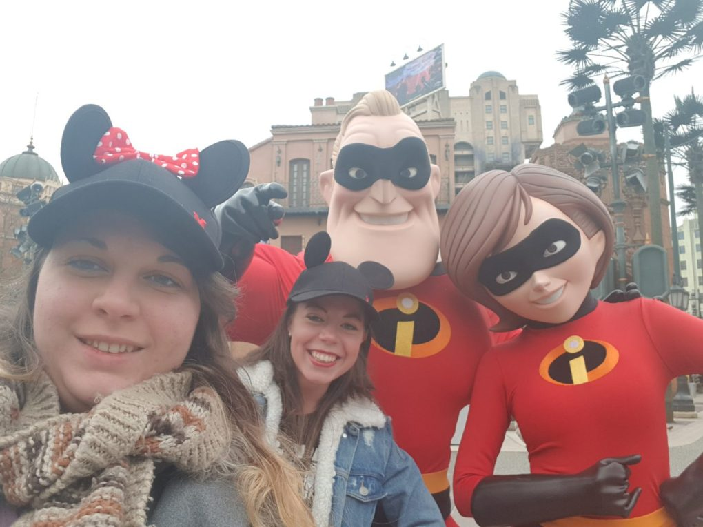 2 girls with Mickey mouse ear hats taking a selfie with Mr and Mrs incredible characters