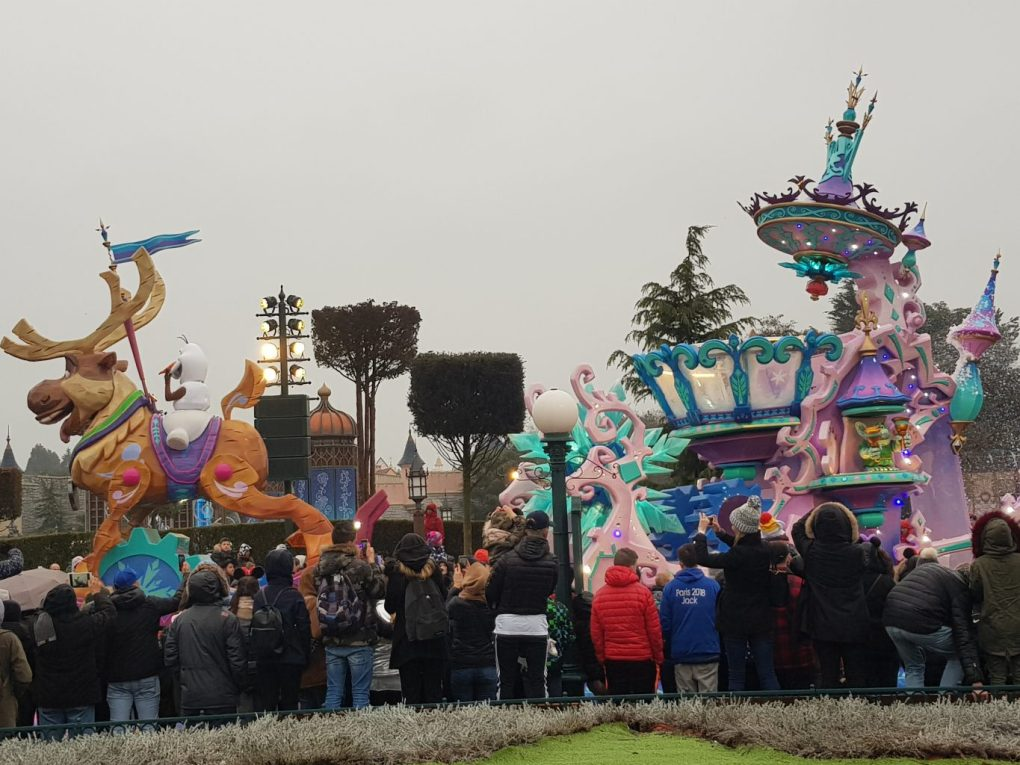 Parade floats from Stars on Parade at Disneyland Paris. Olaf sits on a giant Sven float while a pink and blue ice sledge is pulled behind