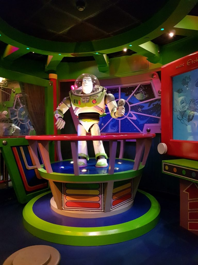 Animated Buzz Light year statue on a platform behind red bars found inside the Buzz Lightyear Laser Blast ride