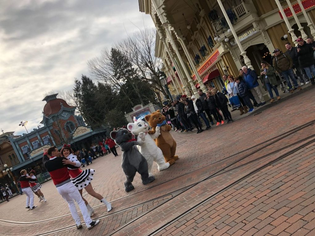 Aristocat kitten characters walking down Mainstreet USA together while dancers dance around them on the guest star parade