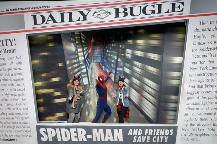two girls posing like they are firing webs out their hands with spiderman dressed in red and black full body suit and a background shows a newspaper page of the Daily Bugle