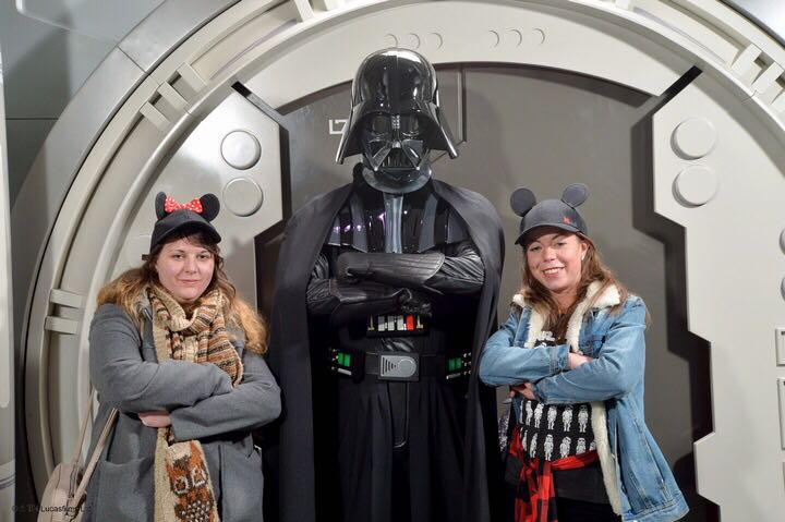 2 girls wearing Mickey ear hats stood next to darth vader in black outfit and helmet. All three are crossing their arms and looking stern