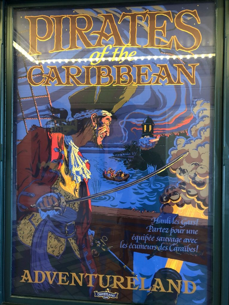 Vintage poster of the Pirates of the Caribbean ride showing a pirate above water where a small boat is moving towards land. At the bottom it says Adventureland