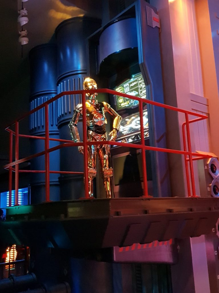 C-3PO a gold metal robot found inside th Star Wars Hyperspace Mountain. He is standing on a platform in front of a computer