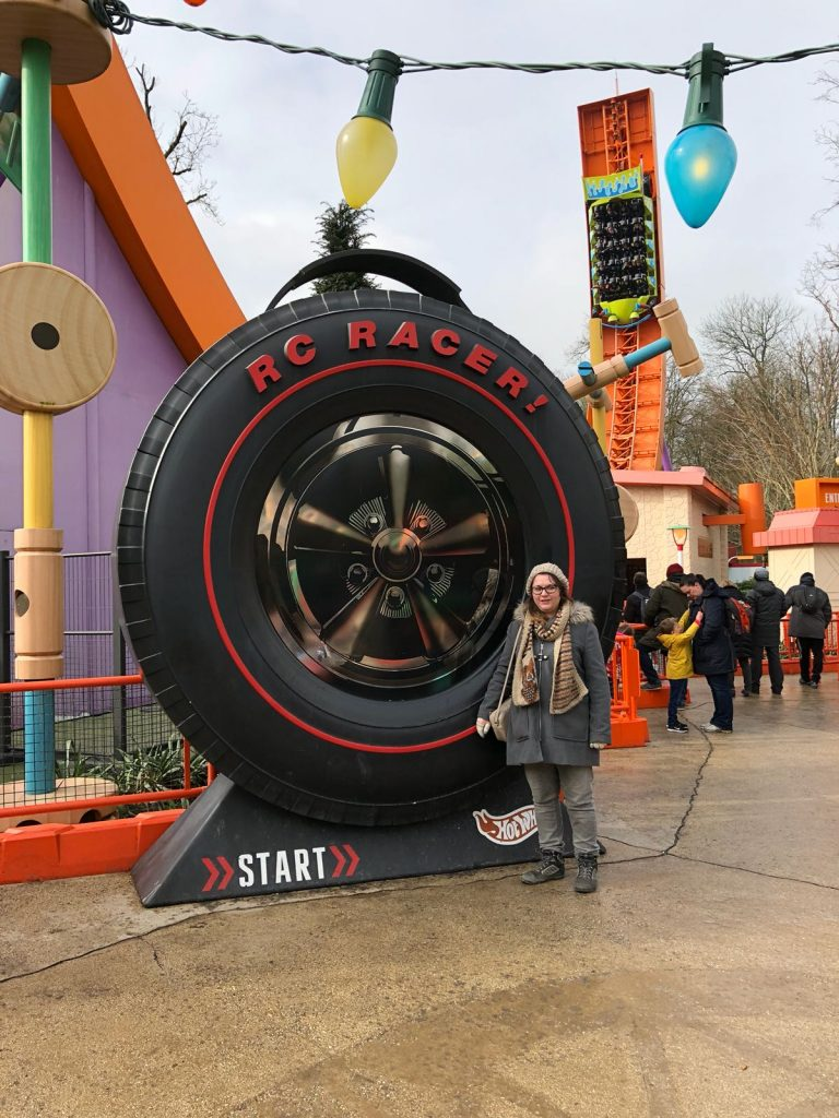 A giant car tyre double the size of the girl stood next to it with an orange U shaped coaster track behind with a green carriage on it in the shape of a hotwheels car.