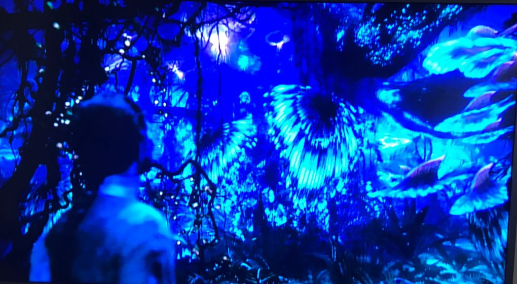 A scene from Avatar where a Na'vi, the blue alien race from the planet Pandora, looks out in a jungle scene full of plants and winged creatures