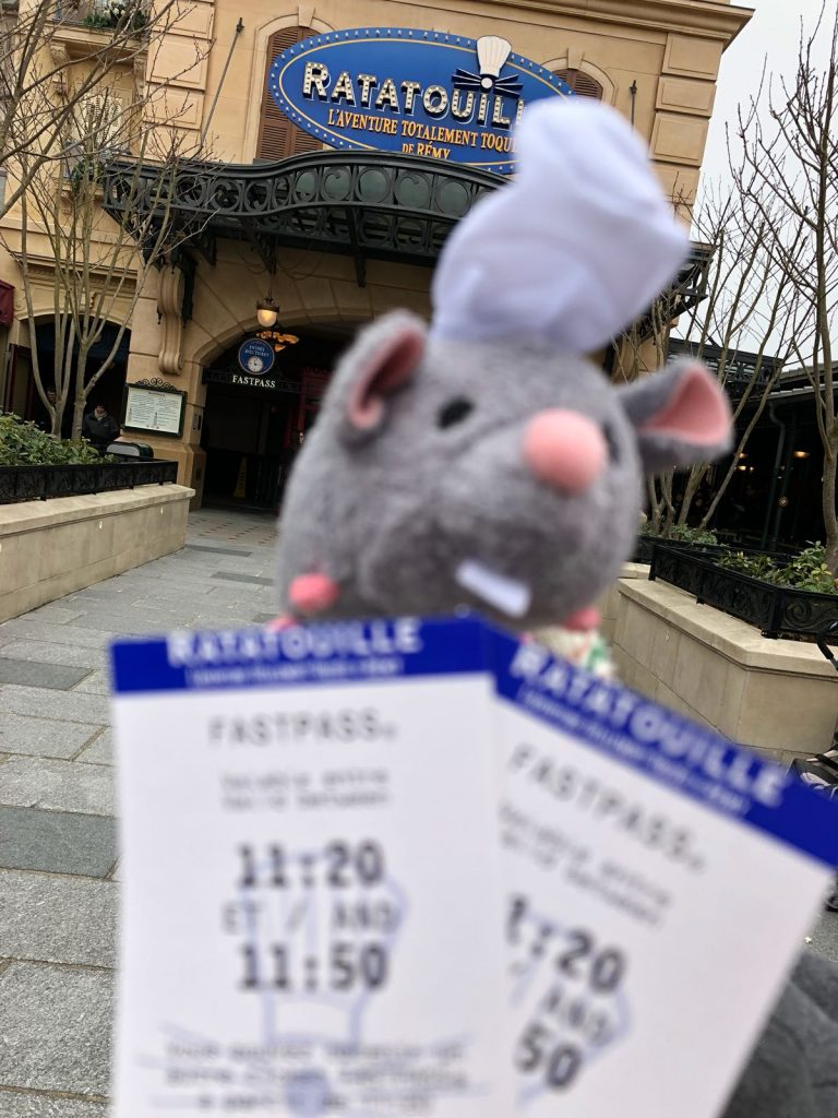 Two Disneyland Paris fastpass tickets for the Ratatouille ride in front ot the door to the ride with its title above. A stuffed mouse wearing a chef house is held above the tickets
