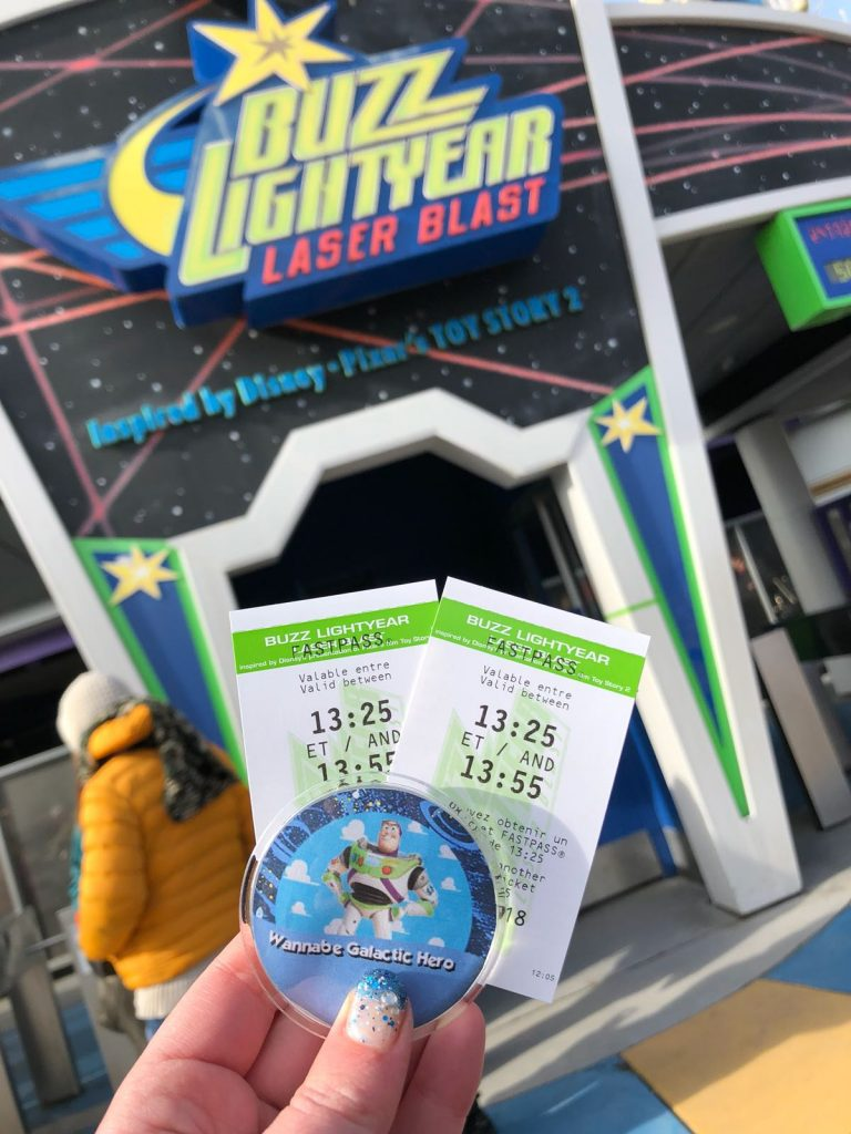 Two Disneyland Paris fastpass tickets for Buzz Lightyear Laser Blast in front ot the door to the ride with its title above.