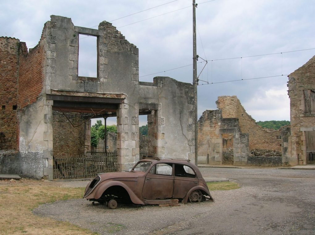 A burned out car in front of the ruins of a building