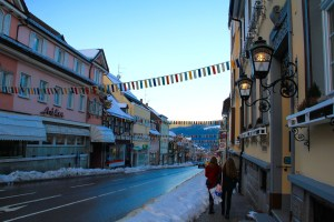 The main street of the town was so quaint with the snow and the flags - Triberg, Germany