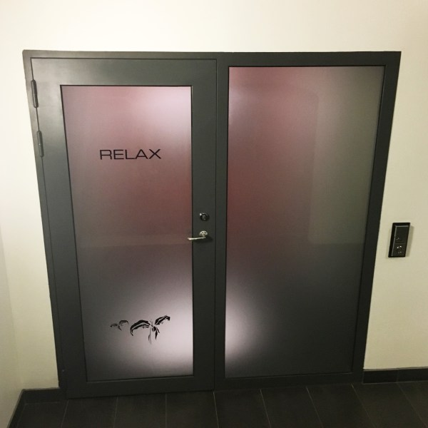 """Door with opaque glass that reads """"RELAX"""" - entrance to sauna"""
