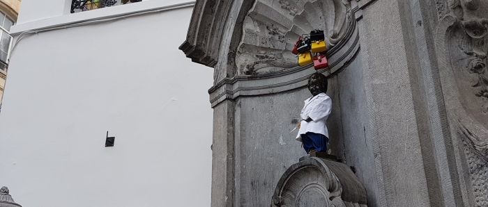 Manneken Pis statue in Brussels, Belgium, dressed in Delvaux for his Fashion Day