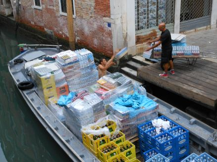 Early in the morning, boats haul their goods to merchants of Venice.
