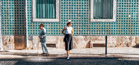 A girl stands in front of a wall bearing green and yellow azulejo tiles as an older woman with a cane shuffles past - Lisbon, Portugal