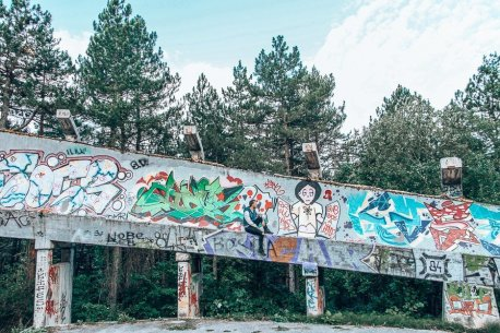 Bevan of the Travel Quandary sits in front of the graffiti on the abandoned bobsled track in Sarajevo, Bosnia & Herzegovina