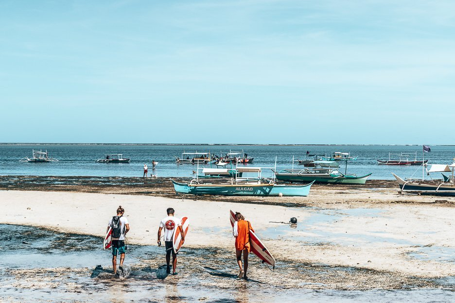 Three surfers holding red and white surfboards navigate low tide to catch the surf off Siargao island