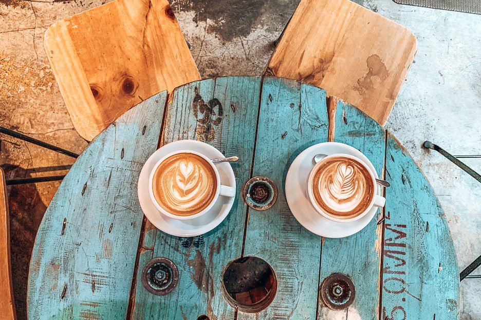 Large flat white and mint mocha on a faded blue wooden table at The Brew Job Coffee, Kowloon, Hong Kong