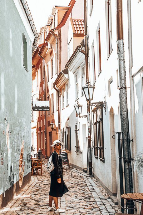Jasmine stands in a cobble stoned laneway in Riga, Latvia