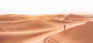 Jasmine walks along the peaks of a sand dune at sunset in the Sahara Desert, Morocco