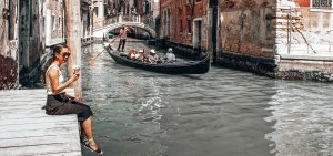 Sitting on a wooden pier eating gelato overlooking a canal in Venice, Italy