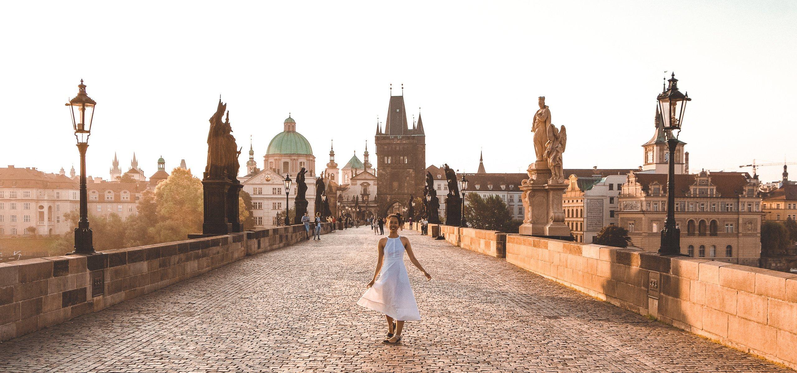 Jasmine twirling in a white dress at sunrise on the Charles Bridge, Prague