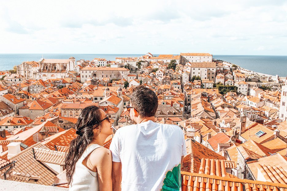 A couple look out over the red roofs of Dubrovnik's Old Town from the city walls, Dubrovnik