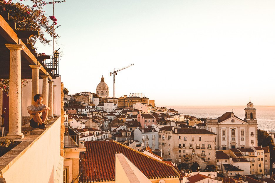 Bevan sits on a miradouro ledge watching sunrise over Lisbon, Portugal