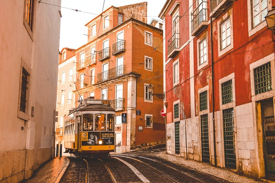 The famous yellow tram 28 trundles down a hill in Lisbon