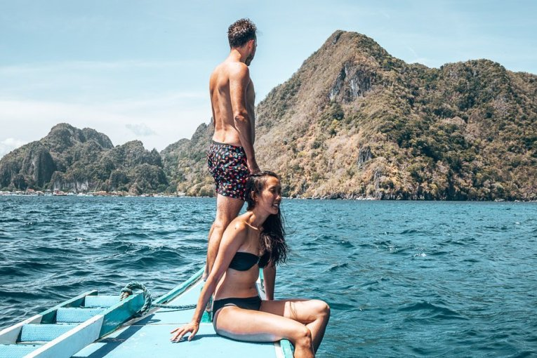 A couple perch on the edge of a boat during a boat tour in El Nido, The Philippines