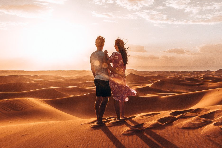 A couple stand on the edge of a sand dune in the Sahara Desert during sunset, Morocco