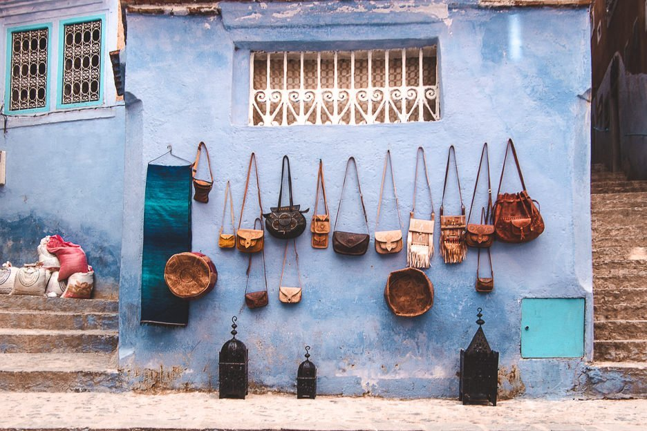 Leather bags hand on a wall for sale in the blue city of Chefchaouen, Morocco