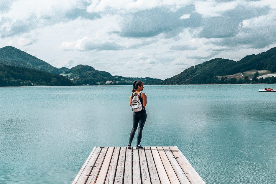 Jasmine stands on a pier looking out over a lake at Fuschal Am See, Austria