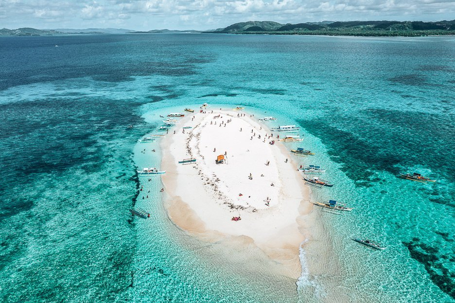 Aerial view of poeple and boats on Naked Island, Siargao