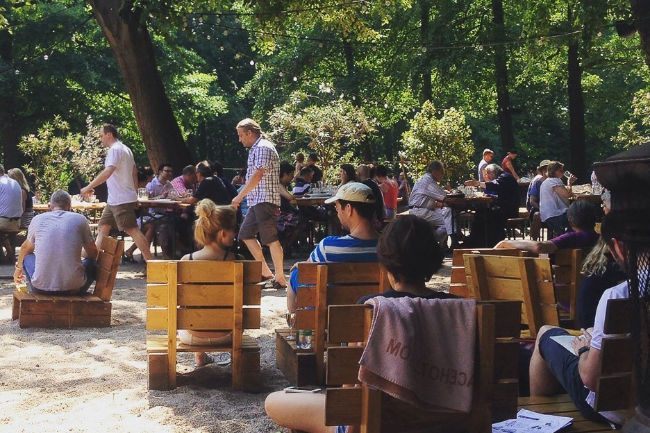 People sit on wooden seats drinking beer in the beergarden at Cafe Am Neuen See, Berlin