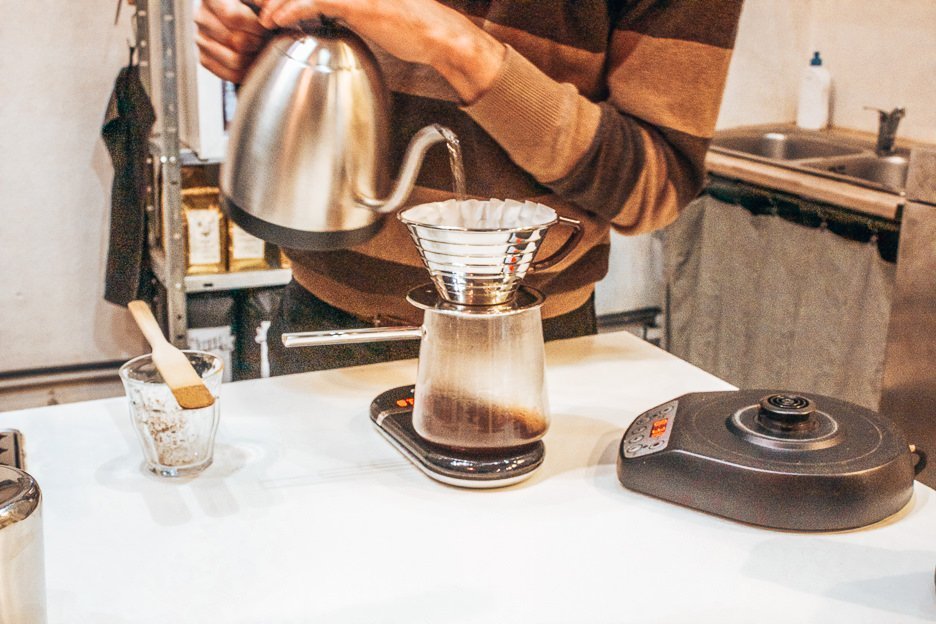 Barista making pour over coffee at Kontakt, Budapest Hungary