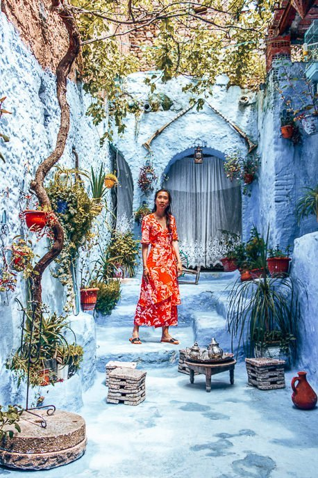 Jasmine of The Travel Quandary posts in a traditional Moroccan courtyard in Chefchaouen Morocco